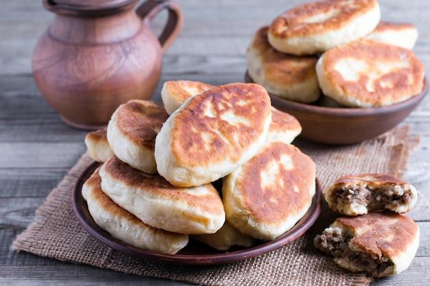 Pasteitjes met aardappelen en vlees op houten tafel