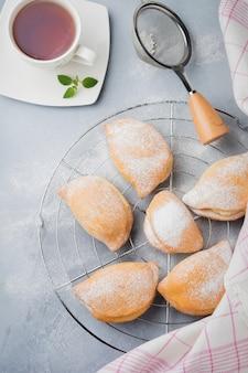 Pasteitjes met kwark en poedersuiker op een grijze steen of betonnen ondergrond. traditioneel russisch gebak sochnik. selectieve aandacht. bovenaanzicht