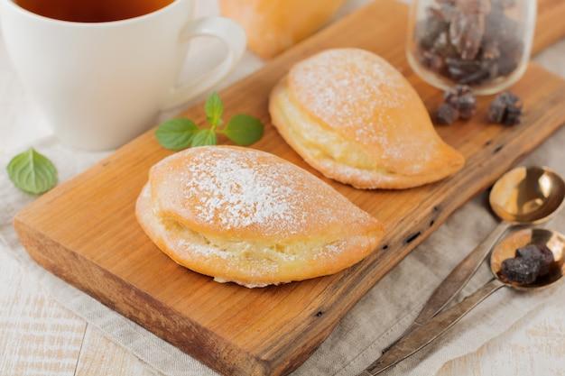 Pasteitjes met kwark en poedersuiker op een lichte houten achtergrond traditionele russische gebak sochnik