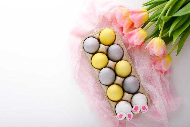 Pastel blauwe en gele paaseieren met roze tulpenboeket, paashazen met roze doekservet op witte achtergrond