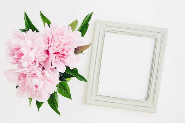 Pastel houten frame versierd met pioenrozen bloemen, lege ruimte voor tekst