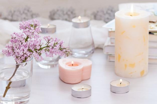 Pastel kamer interieur met brandende handgemaakte kaars, boeken, bloemen. gezellig en ontspannen concept.