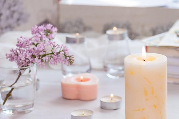 Pastel kamer interieur met brandende handgemaakte kaars, boeken, bloemen.