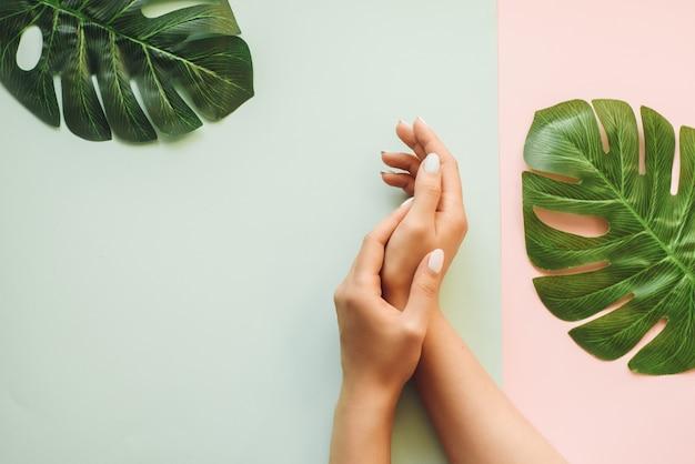 Pastel manicure op een blauwe en roze achtergrond met palmbladeren. tropische achtergrond met handen van de vrouw