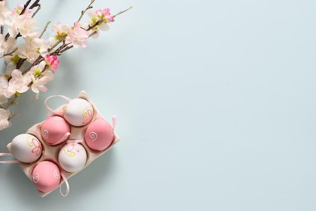 Pastel paaseieren en bloeiende lentebloemen op blauw.