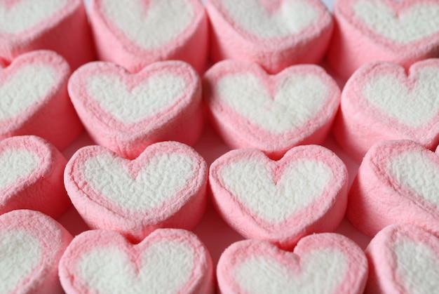 Pastel roze en witte hartvormige marshmallow snoepjes voor achtergrond opgesteld