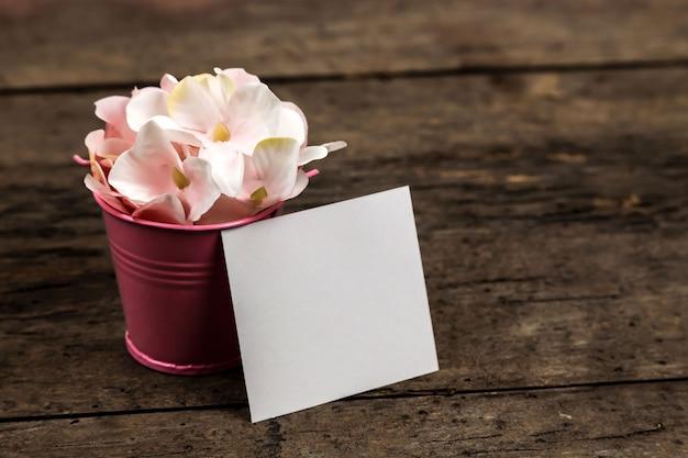 Pastel roze hortensia bloemen in een kleine emmer en een stuk papier op hout. copyspace voor tekst