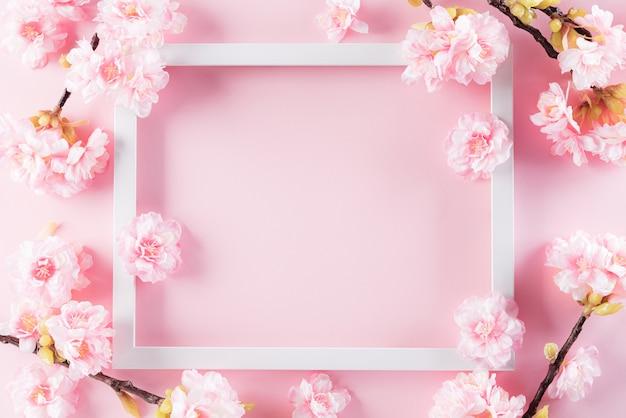 Pastel roze kleuren achtergrond met fotolijst en bloesem bloemen plat lag patronen.