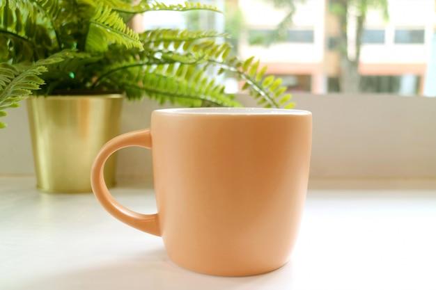 Pastel roze koffiemok met ingemaakte varens op een tafel bij het raam