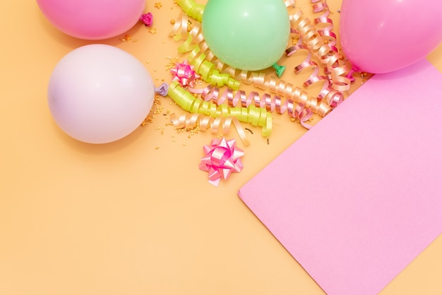 Pastel roze tafel met frame van ballonnen en confetti voor verjaardag bovenaanzicht. plat leggen samenstelling.