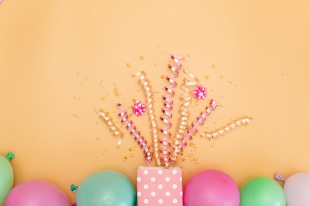Pastel roze tafel met frame van ballonnen en confetti voor verjaardag bovenaanzicht