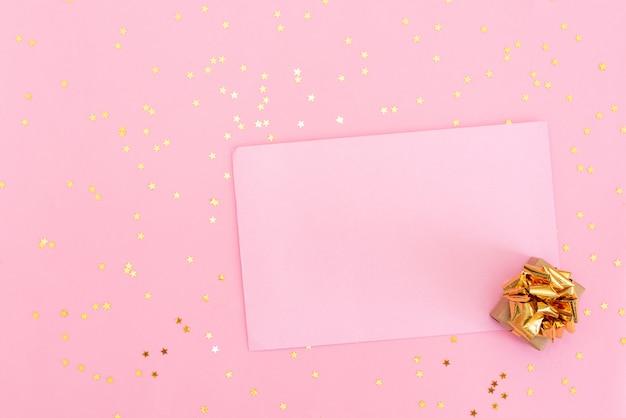 Pastel roze tafel met kleurrijke ballonnen en confetti voor verjaardag bovenaanzicht. vlakke lay-stijl.