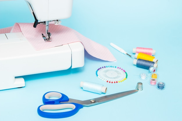 Pastelkleur achtergrond, naaister en designer bureau, handgemaakte accessoires. dradenrol, schaar en spelden.