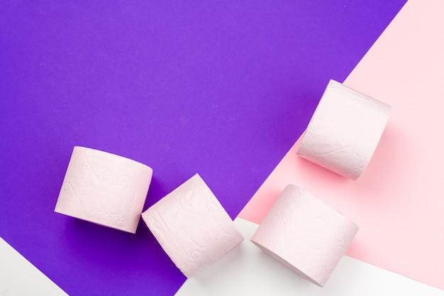 Pastelkleur roze toiletpapier op de heldere achtergrond van het kleurenblok