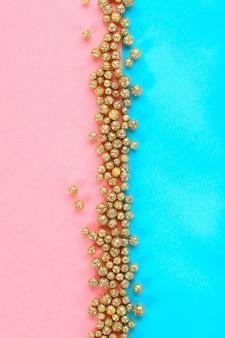Pastelkleurachtergrond met glanzende decoratieve sterren en ballen wordt verfraaid die