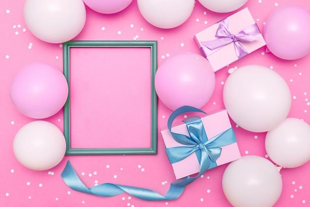 Pastelkleurige ballonnen en witte confetti op roze