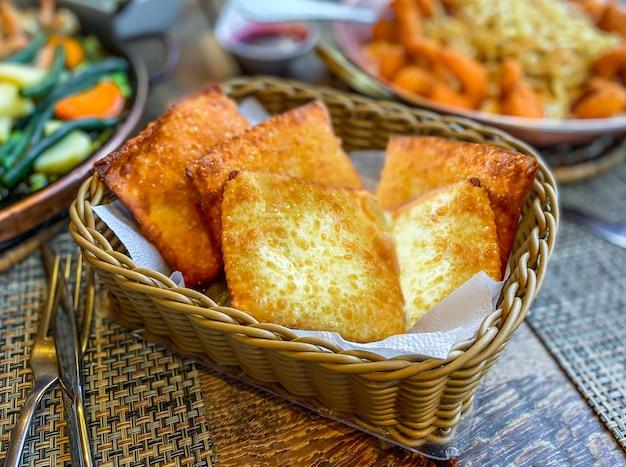 Pastelkleurige, braziliaanse snack gevuld met gehakt, garnalen, kaas en krab in een rieten mand.
