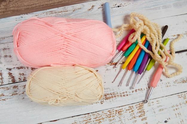Pastelkleurige garens om te haken en haken op een houten ondergrond