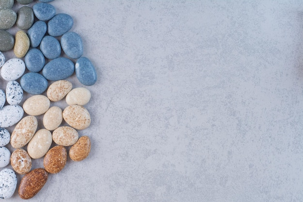 Pastelkleurige stenen voor het knutselen op een betonnen ondergrond.
