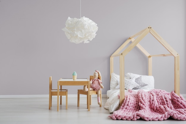 Pastelroze meisjeskamer met een modern, houten bed, een kleine tafel en een knuffeldier dat ernaast zit