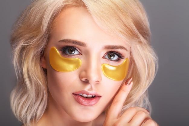 Patch onder de ogen. mooi vrouwengezicht met gouden hydrogelpleisters, opheffend antirimpelcollageenmasker.