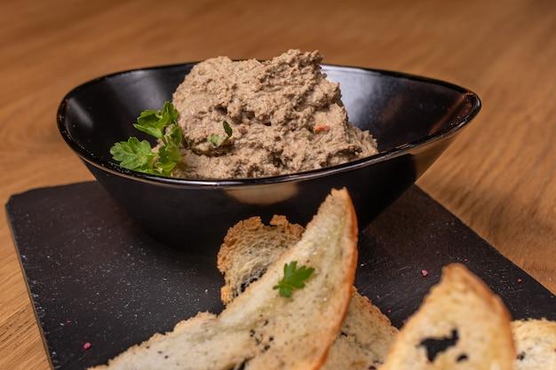 Pate van runderlever en vlees met kruiden in een zwarte plaat met toast.