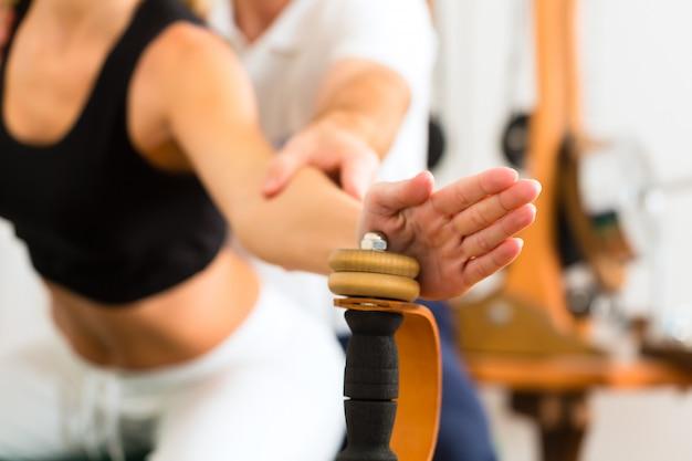 Patiënt bij de fysiotherapie die fysieke oefeningen maakt