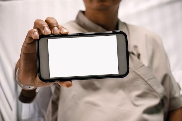 Patiënt die de monitor van smartphone in het ziekenhuis toont