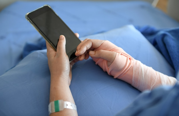 Patiënt die een spalk in de arm draagt. hij speelt smartphone.
