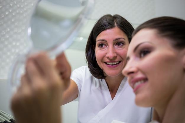 Patiënt die haar tanden in spiegel controleert
