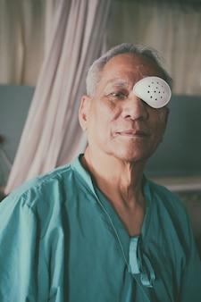 Patiënt die het oog bedekt met een beschermend schild na een cataractoperatie aan de ogen