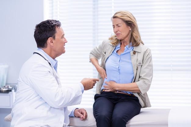 Patiënt die lijdt aan buikpijn tijdens het raadplegen van de arts