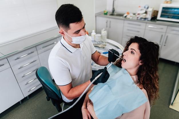 Patiënt die tanden krijgt die bij de tandarts schoonmaken