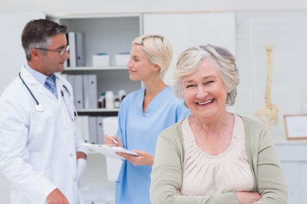 Patiënt die terwijl arts en verpleegster glimlachen die op achtergrond bespreken