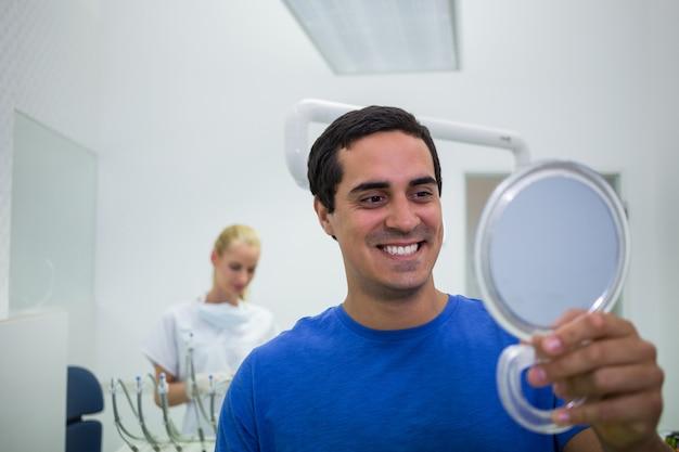 Patiënt die zijn tanden in spiegel controleert