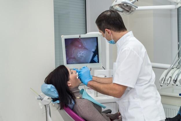 Patiënt en tandarts scherm in de tandheelkunde kijken