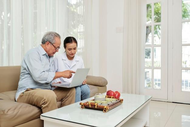 Patiënt en verpleegster met behulp van laptop
