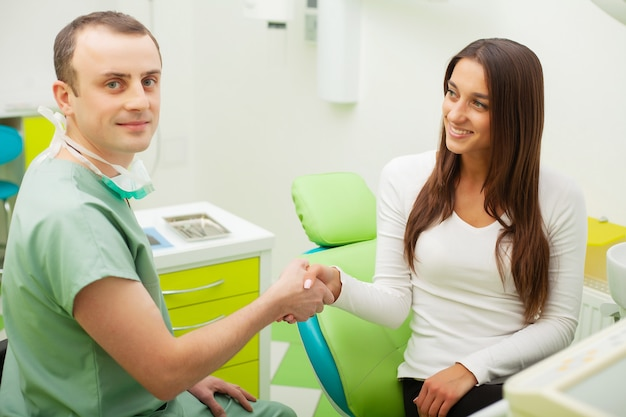 Patiënt in de tandheelkunde. mooie vrouw die haar tandarts in kliniek bezoekt