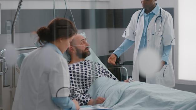 Patiënt in gesprek met artsen terwijl hij in bed ligt tijdens herstel van ziekte