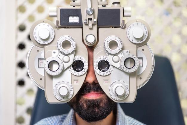 Patiënt in moderne oftalmologiekliniek die de oogvisie controleert.