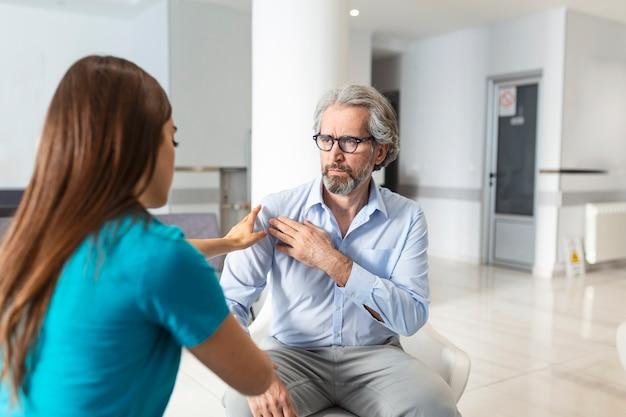 Patiënt klaagt bij de dokter over zijn schouderpijn en andere symptomen. jonge vrouwelijke arts diagnosticeerde haar patiënt. ziekenhuis wachtkamer