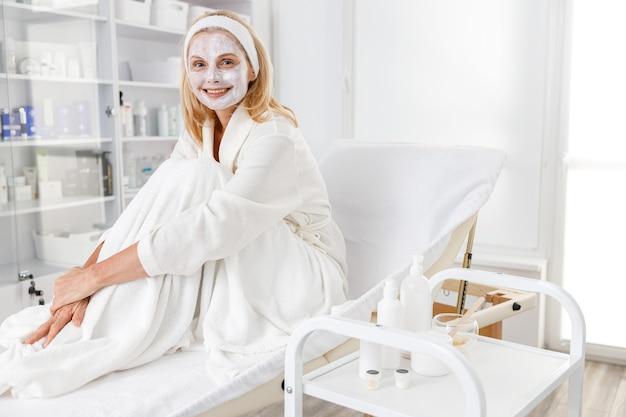 Patiënt liggend op de bank wacht op resultaten van huidverzorgingsbehandeling. effectieve werkwijze. portret van mooie vrouw in witte badjas zittend op daybed.