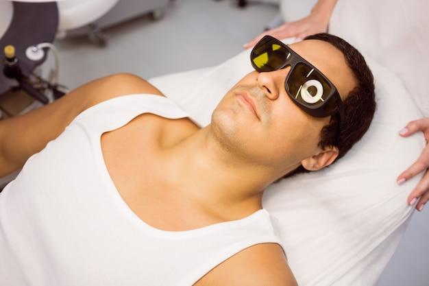 Patiënt met beschermende bril liggend voor behandeling
