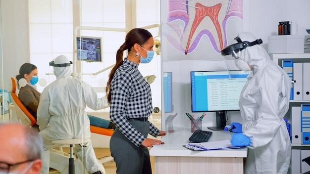 Patiënt met beschermingsmasker die afspraak maakt voor tandbehandeling bij een pandemie van het coronavirus. stomatoloog werkzaam in achtergrondassistent die overall draagt, gezichtsschild in tandheelkundige kliniek met nieuw normaal