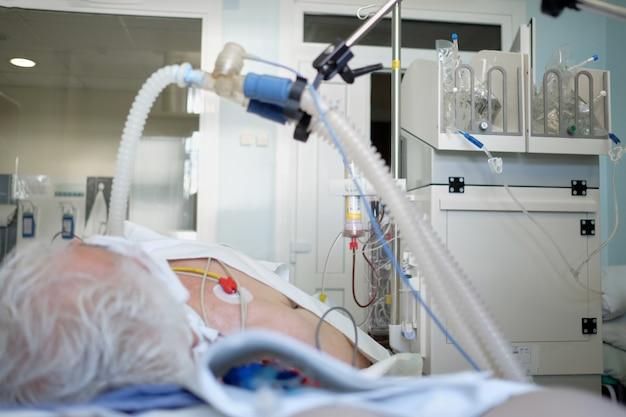Patiënt met coronaviruspneumonie in kritieke toestand. geïntubeerde senior onder ventilator liggend in coma op intensive care afdeling.