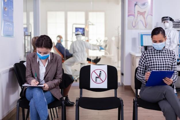 Patiënt met gezichtsbeschermingsmasker die op registratieformulier schrijft in de stomatomoly-kliniek, zittend bij de receptie met respect voor sociale afstand