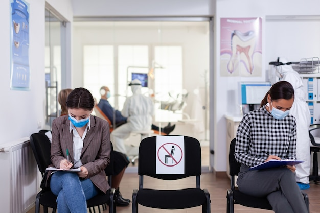 Patiënt met gezichtsbeschermingsmasker die op registratieformulier schrijft
