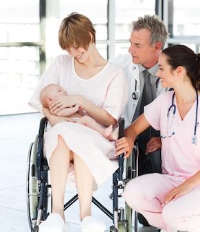Patiënt met haar pasgeboren baby en artsen