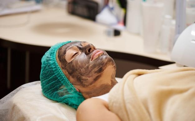 Patiënt met zwart masker op gezicht bij de afspraak van de schoonheidsspecialiste