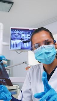 Patiënt pov die tandarts bekijkt die om tandröntgenstraal vraagt die tandenbeeld toont. stomatologiespecialist met beschermend masker, werkzaam in moderne stomatologische kliniek, radiografie van tand uitleggend